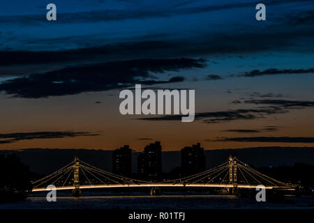 London, UK. 31st October, 2018. The sun sets behind Albert bridge and Chelsea Harbour. Credit: Guy Bell/Alamy Live News - Stock Photo