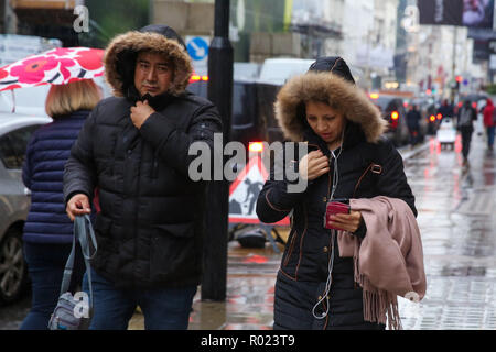 Oxford Street, London, UK. 1st Nov, 2018. Shoppers shelter from the rain beneath umbrellas as rain falls in London. Credit: Dinendra Haria/Alamy Live News - Stock Photo