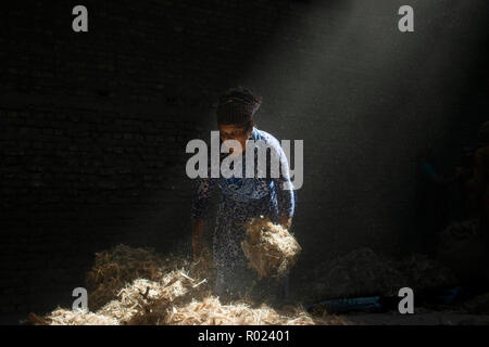 Sun rays enter through the rooftop while Jute mill worker sorting out small pieces of jutes. Bangladesh used to be known for it's Jute. In recent years Bangladesh and many other country considering jute as the new possibilities to replace many daily goods and make bags out of jute to replace plastics. - Stock Photo