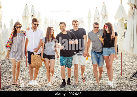 holidays, vacation. group of friends having fun on beach, walking, drink beer, smiling and hugging - Stock Photo