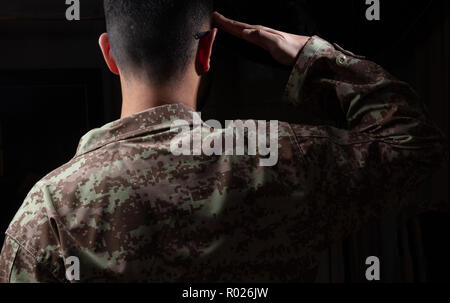 US Army. Young soldier saluting standing on black background - Stock Photo