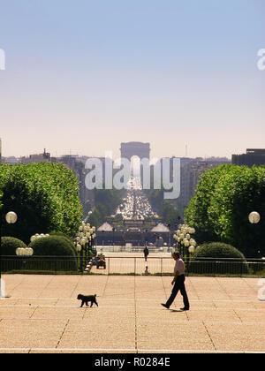 A dog walks his man across the Axe Historique from Esplanade du Général de Gaulle, la Défense, Paris.  View towards the Arc de Triomphe and Place de l'Étoile - Stock Photo