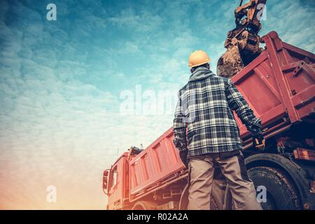 Ground Works Operation. Construction Worker in Front of Dump Truck Loaded by Excavator. Heavy Duty Machinery. Soil Removing. - Stock Photo