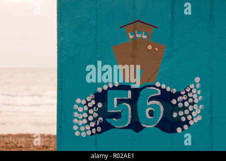 Brown painted boat on on a blue english beach hut with the number 56 and the beach and sea in the background - Stock Photo