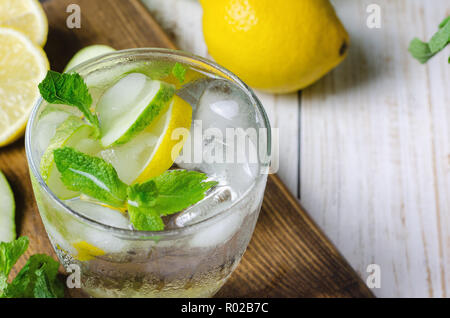 Cold lemonade with lemon, mint and cucumber in glass. - Stock Photo