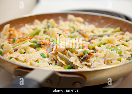 Delicious looking pasta dish in a skillet being cooked and stirred, with salmon, pasta, asparagus and peas - Stock Photo