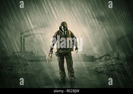 Gas masked survival man coming with arms on his hand  in a demolished dark environment   - Stock Photo