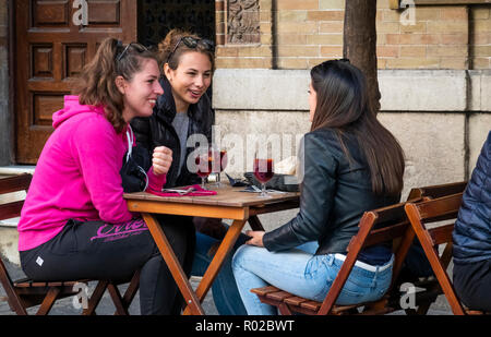 Three young women enjoying a talk and some sangria at an outside table of a bar in Seville, Spain - Stock Photo