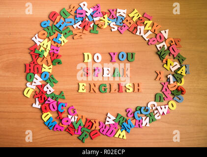 Do you speak english wooden letters around a pile of other over office table board surface - Stock Photo
