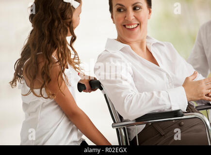 Senior woman in a wheelchair,  receiving a visit from her granddaughter. - Stock Photo