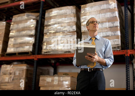 Thoughtful businessman taking notes on a clipboard in a warehouse. - Stock Photo