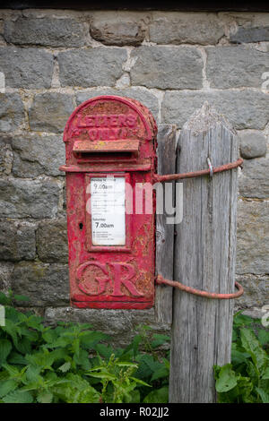 Old postbox strapped to a pole in the countryside, Nidderdale, North Yorkshire. - Stock Photo