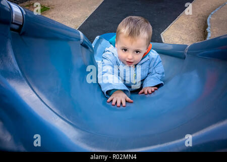 Little young Caucasian boy climbing up the big outdoor slide on a playground - Stock Photo
