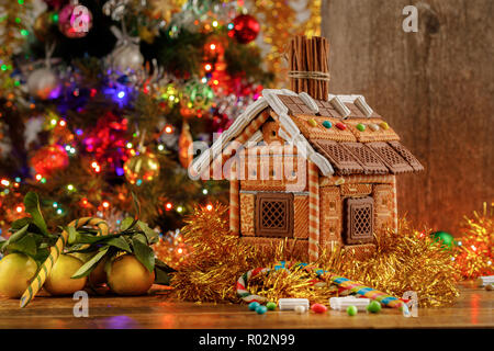 Beautifully decorated Christmas tree and gingerbread house with sweets. New Year's atmosphere. - Stock Photo