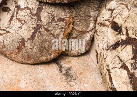 Bakery - gold rustic crusty loaves of bread and buns on black chalkboard background. Still life captured from above (top view, flat lay). - Stock Photo