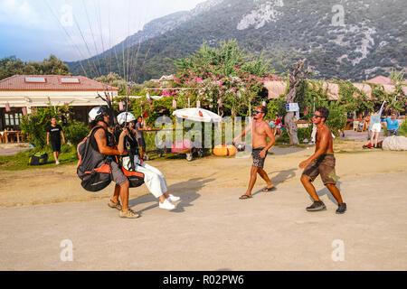 Fethiye, Mugla/Turkey - August 19 2018:  Tandem paragliders are landing on Belcekiz Beach in Oludeniz. - Stock Photo