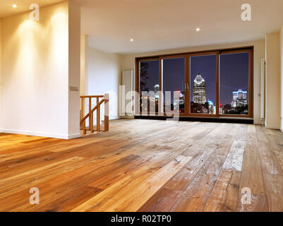 Empty big living room interior with wooden floor and view on night city lights - Stock Photo