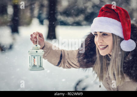 Christmas lantern - beautiful girl in Santa hat on winter forest - Stock Photo