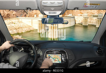 Driving a car while using the touch screen of a GPS navigation system towards Hoover Dam and Colorado River at the border between Nevada and Arizona,  - Stock Photo