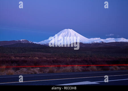 Mt Ngauruhoe at dawn, and tail lights on Desert Road, Tongariro National Park, Central Plateau, North Island, New Zealand - Stock Photo