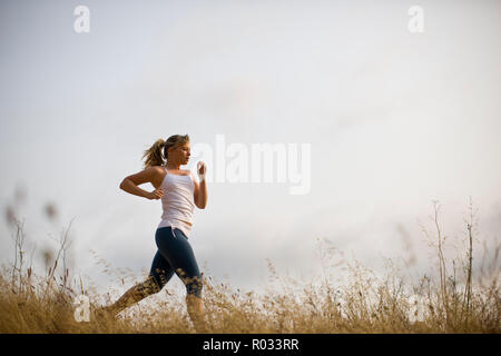 Teenage girl running along a track in a field. - Stock Photo