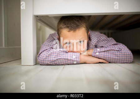 Portrait of a boy lying on his stomach while hiding underneath a wooden bed. - Stock Photo