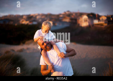 Man giving his son a shoulder ride on the beach - Stock Photo