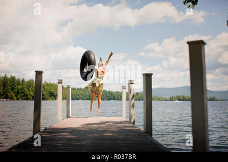 Woman with inner tube,  jumping off a jetty into a lake. - Stock Photo