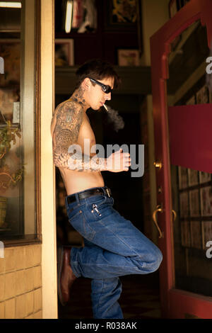 Man standing in doorway of tattoo parlour smoking a cigarette. - Stock Photo