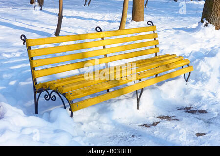 Yellow wooden bench among the snowbanks in winter park on a sunny fine day - Stock Photo