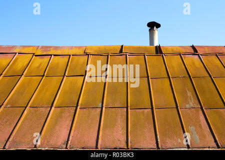 Detail of the roof covered with old metal painted tile