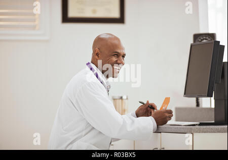 Laughing male doctor holding a box of medication inside his office. - Stock Photo