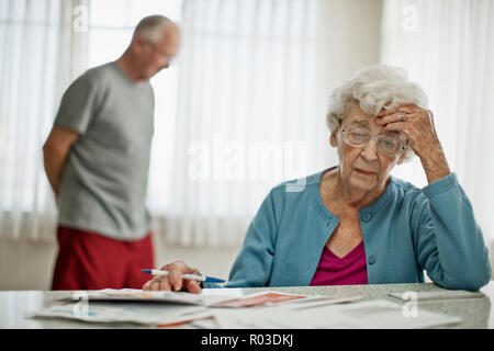 Anxious elderly couple worry about how they will pay all the bills they have received. - Stock Photo