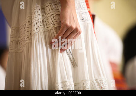 Details with the hand of a woman singing in a choir holding a tuning fork - Stock Photo