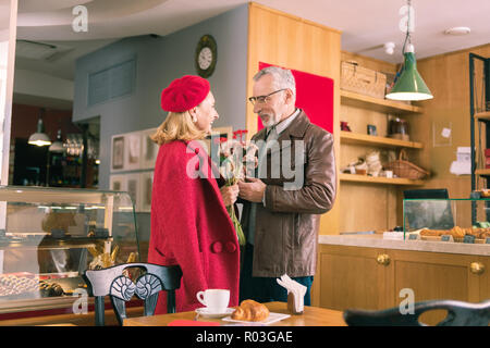 Beaming lady wearing red beret receiving flowers from husband - Stock Photo