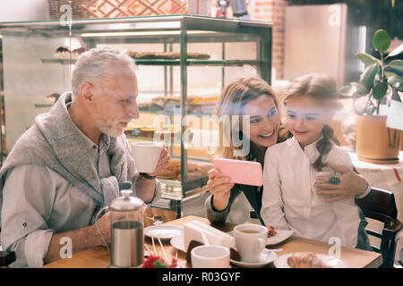 Beaming grandmother showing her cute girl some family photos - Stock Photo