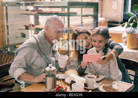 Grandmother holding her pink smartphone showing photos to granddaughter - Stock Photo