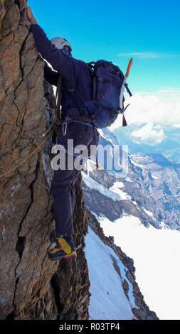 extreme mountain climber on an exposed and vertical rock and snow face on his way to a high alpine mountain peak - Stock Photo