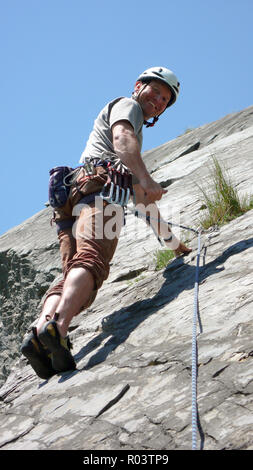 mountain guide rock climber on a slab limestone climbing route in the Alps of Switzerland on a beautiful day - Stock Photo