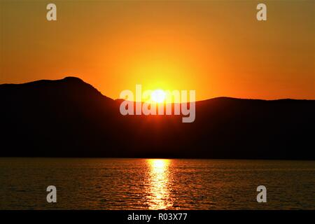 Sunset over Dalyan, Turkey, taken from a boat in a lake. - Stock Photo