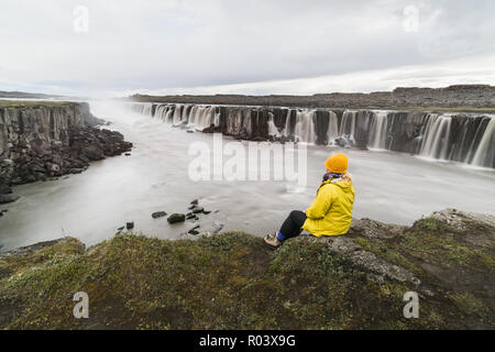 Woman in yellow raincoat sitting standing on the cliff edge next to Selfoss waterfall in Vatnayokull national park, Iceland. - Stock Photo