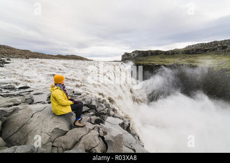 Woman in yellow raincoat sitting standing on the cliff edge next to Dettifoss waterfall in Vatnayokull national park, Iceland. - Stock Photo