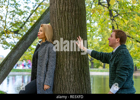Couple talking seriously outdoors in a park with a green background - Stock Photo