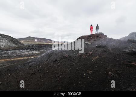 Woman and man figures standing in Krafla volcano lava field around Leirhnjukur mountain peak, Iceland. - Stock Photo