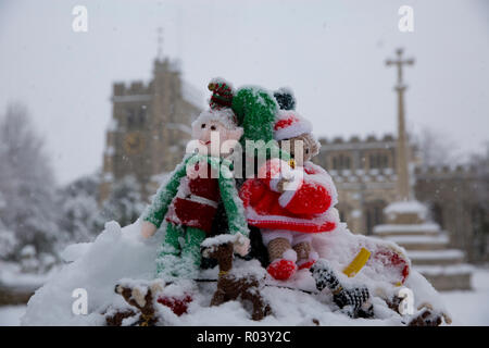 Knitted Christmas decoration. War memorial and Parish Church of St Peter and St Paul, in the market town of Tring, Hertfordshire, England, winter snow - Stock Photo