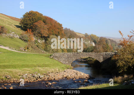 View down River Swale as it flows under a stone bridge near Wain Wath Force on a sunny autumn day with trees in autumn tints on the hillside. - Stock Photo