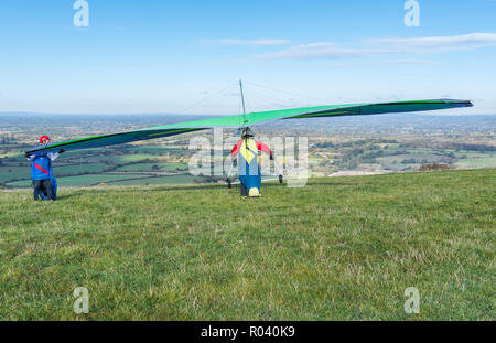 Man taking off from hills on a hang glider at the Devil's Dyke on the South Downs in East Sussex, England, UK. - Stock Photo