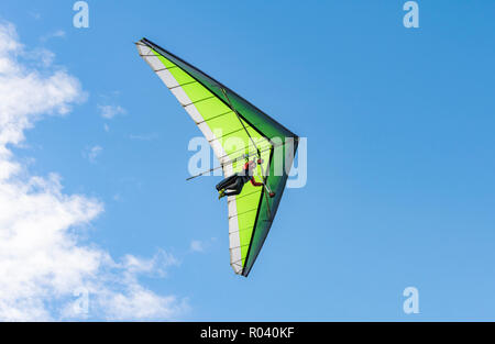 Man hang gliding in Autumn with blue sky at the South Downs in East Sussex, England, UK. - Stock Photo