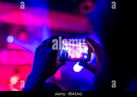 the person registers the night life by creating a movie using the camera built into the smartphone - Stock Photo