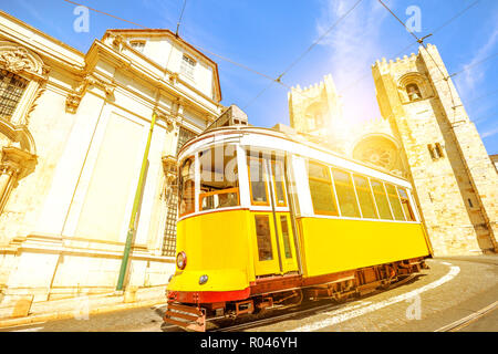 Historic yellow tram line in front of Lisbon Cathedral in Alfama district, Lisbon, Portugal. Lisbon street with typical vintage tram and Se de Lisboa. Sunset light shot. - Stock Photo